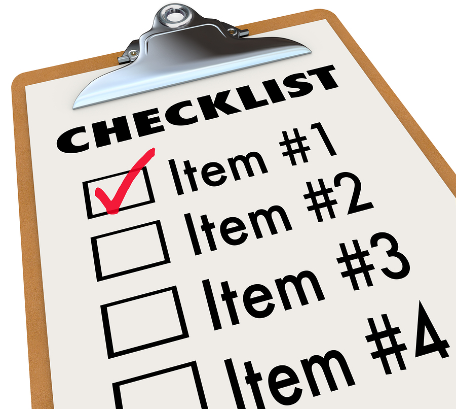 A checklist on a wood and metal clipboard with a check next to t